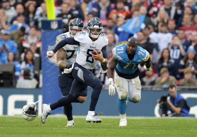 Titans quarterback Marcus Mariota (8) is pursued by helmetless Chargers defensive tackle Damion Square (71) on an 11-yard run in the fourth quarter Sunday.