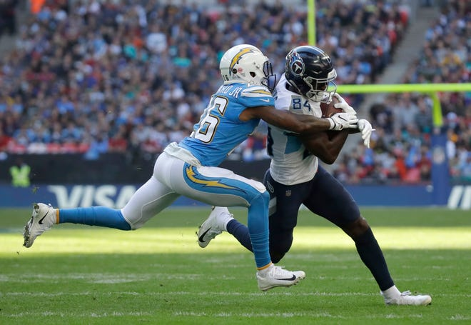 Titans wide receiver Corey Davis (84) is tackled by Chargers cornerback Casey Hayward (26) during the first half of a game Oct. 21 at  Wembley Stadium in London.
