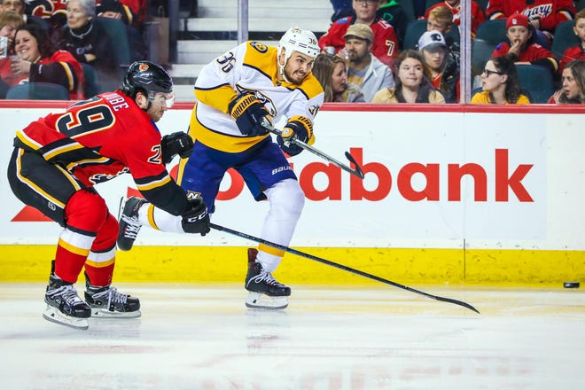 Predators center Zac Rinaldo (36) shoots the puck against the Flames during the second period Friday.
