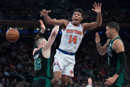 New York Knicks guard Allonzo Trier (14) is fouled as the drives to the basket against Boston Celtics forward Aron Baynes (46) and Boston Celtics forward Jayson Tatum (0) during the first half of an NBA basketball game, Saturday, Oct. 20, 2018, at Madison Square Garden in New York.