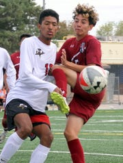 Senior Wildcat midfielder Christopher Cardoza, right, gets tangled up with a Centennial Hawks player in Saturday's 1-0 Deming High victory.