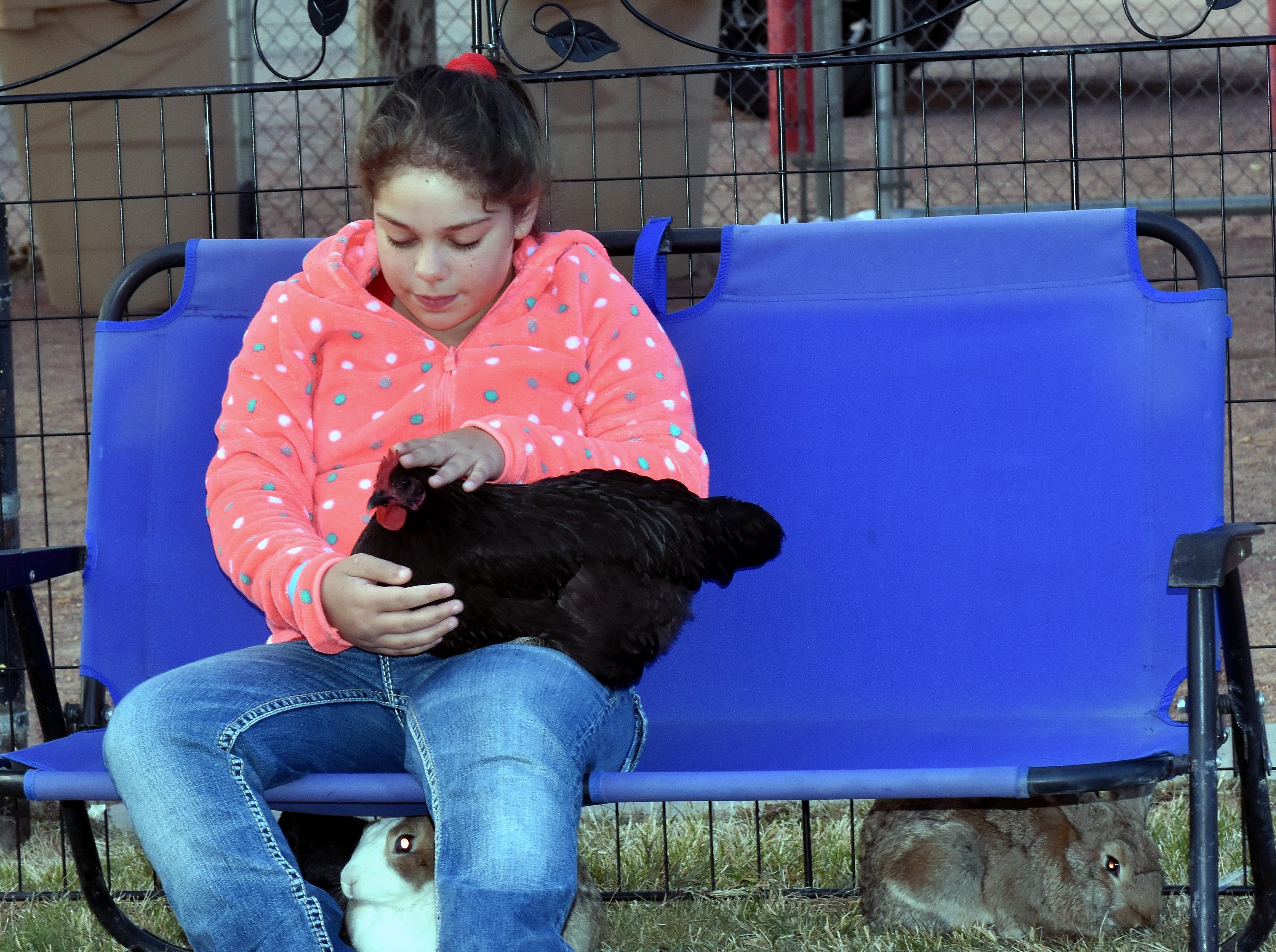 Autumn Rain Jackson, 12, from Las Cruces holds one of the many pets for kids to play with provided by Barnyard Buddies at the Las Cruces Country Music Festival on Saturday, Oct. 20, 2018.