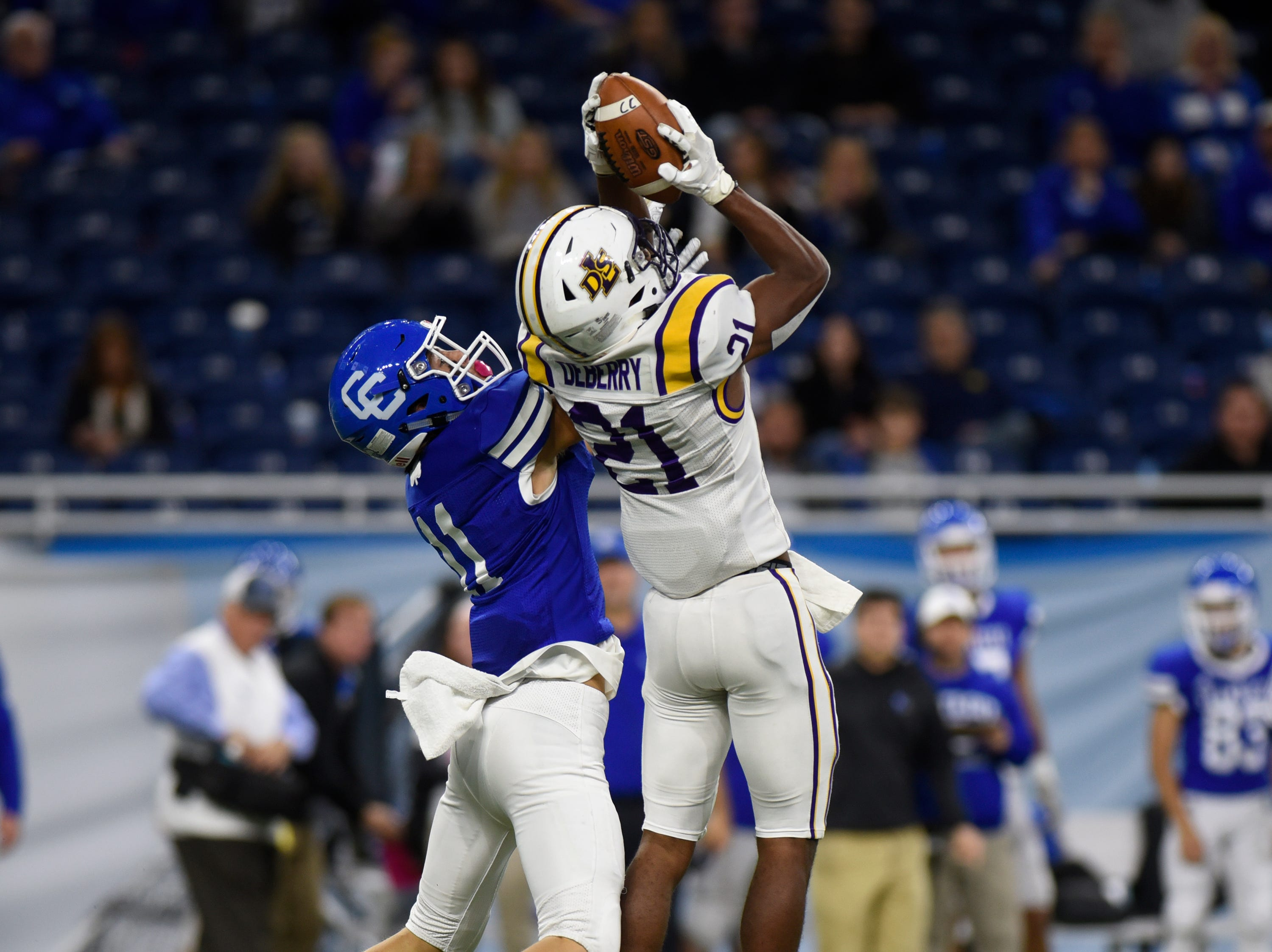 Warren De La Salle's Joshua DeBerry (21) intercepts a pas intended for Detroit Catholic Central WR/DB Nate Anderson (11) during Catholic League Prep Bowl AB Division championship game at Ford Field Oct. 20, 2018.