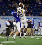 De La Salle's Joshua DeBerry (21) intercepts a pass intended for Detroit CC's Nate Anderson (11) during Catholic League Prep Bowl A-B Division championship game on Oct. 20 at Detroit's Ford Field.