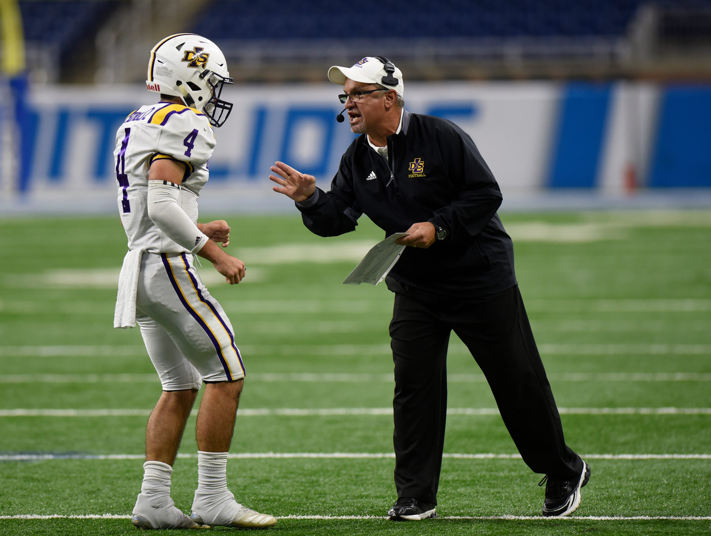 Warren De La Salle football head coach Mike Giannone gives a play to quarterback back Nolan Schultz (4) during Catholic League Prep Bowl AB Division championship game at Ford Field Oct. 20, 2018.