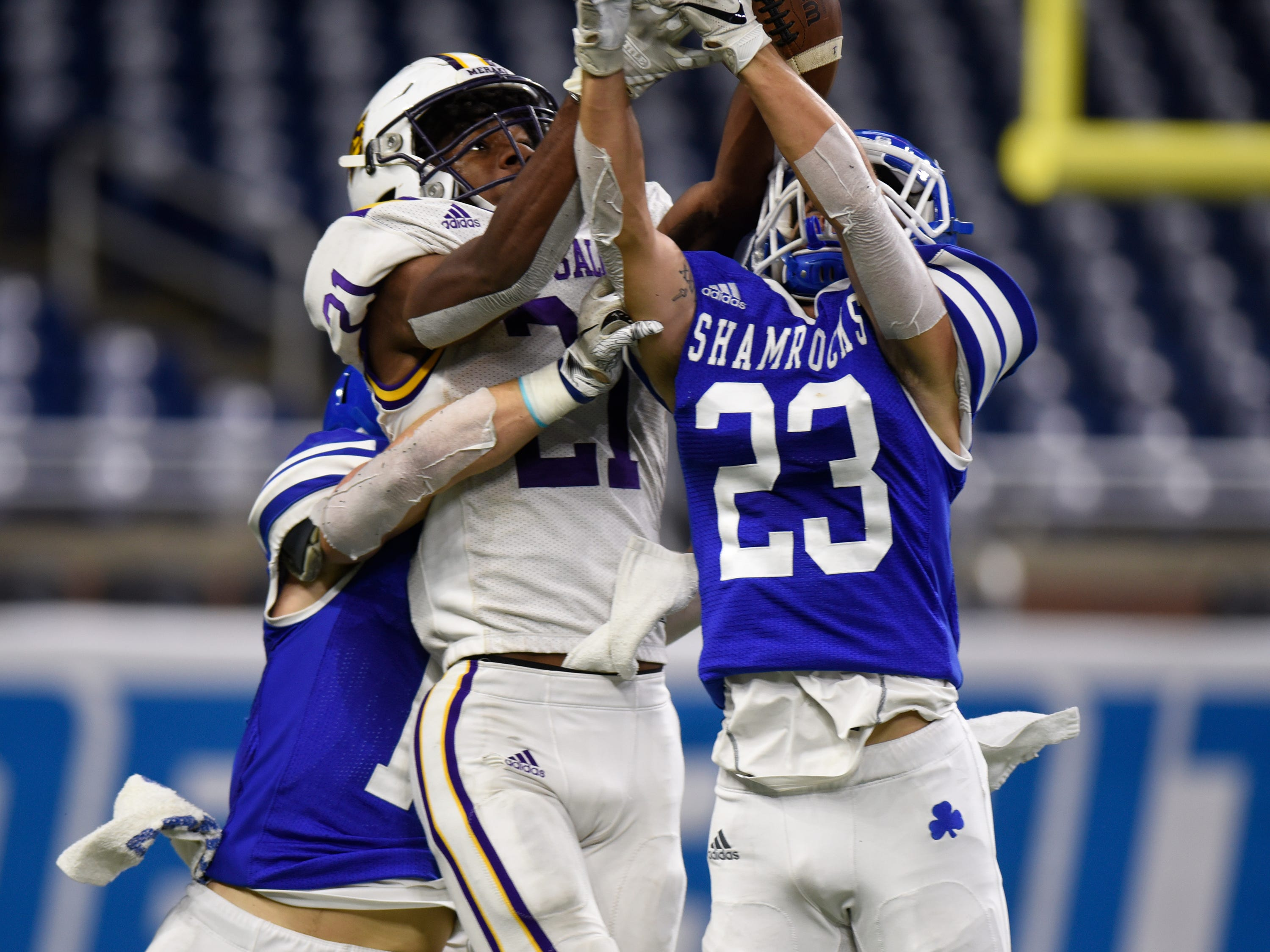 Warren De La Salle's Joshua DeBerry (21) breaks up a pass meant for Detroit Catholic Central's Parker Bohland (23) during Catholic League Prep Bowl AB Division championship game at Ford Field Oct. 20, 2018.