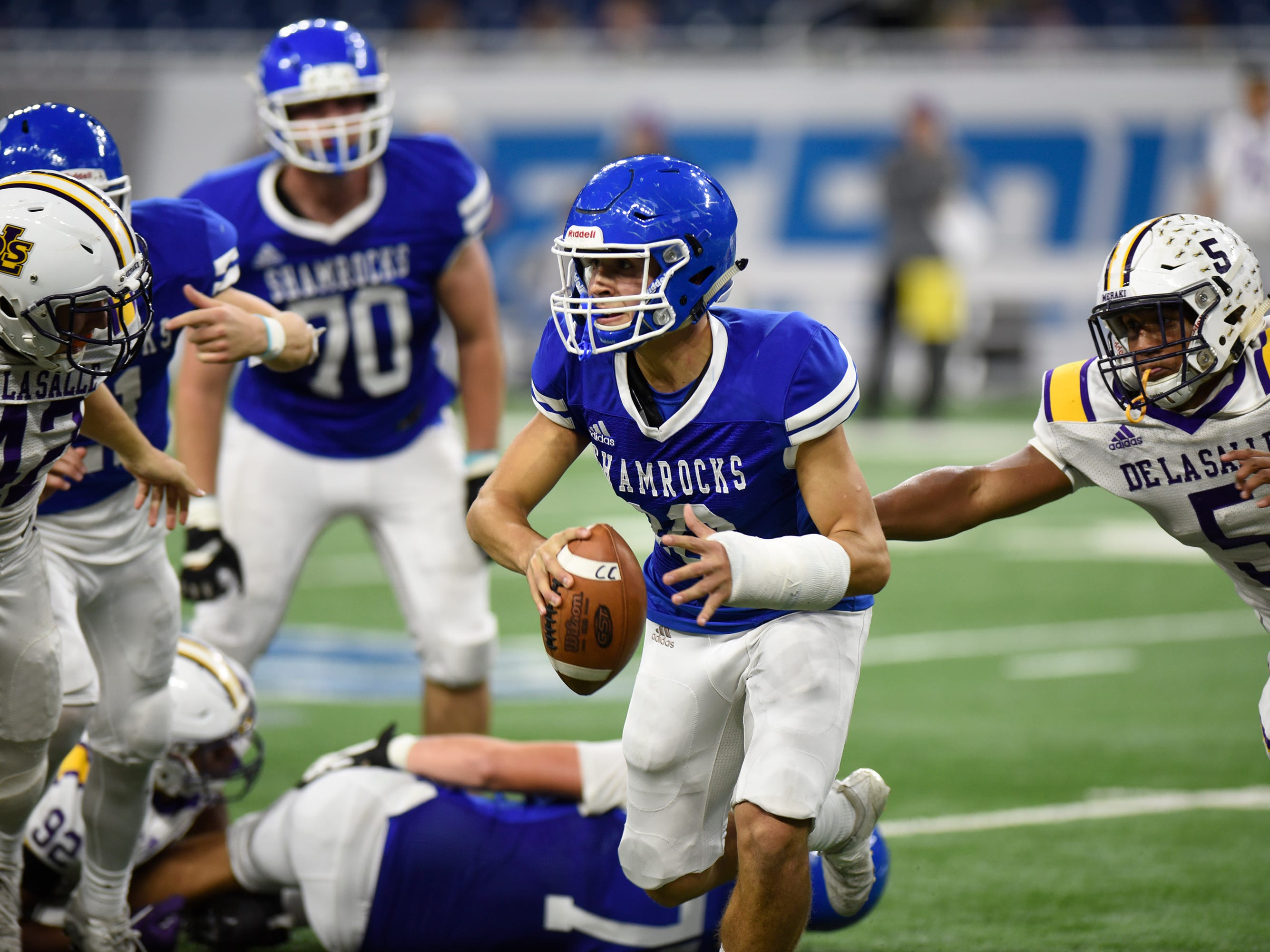 Detroit Catholic Central QB Marco Genrich (10) is chased by Warren De La Salle defenders David Stegner (42) and Devin Campbell (5) during the Catholic League Prep Bowl AB Division championship game at Ford Field Oct. 20, 2018.