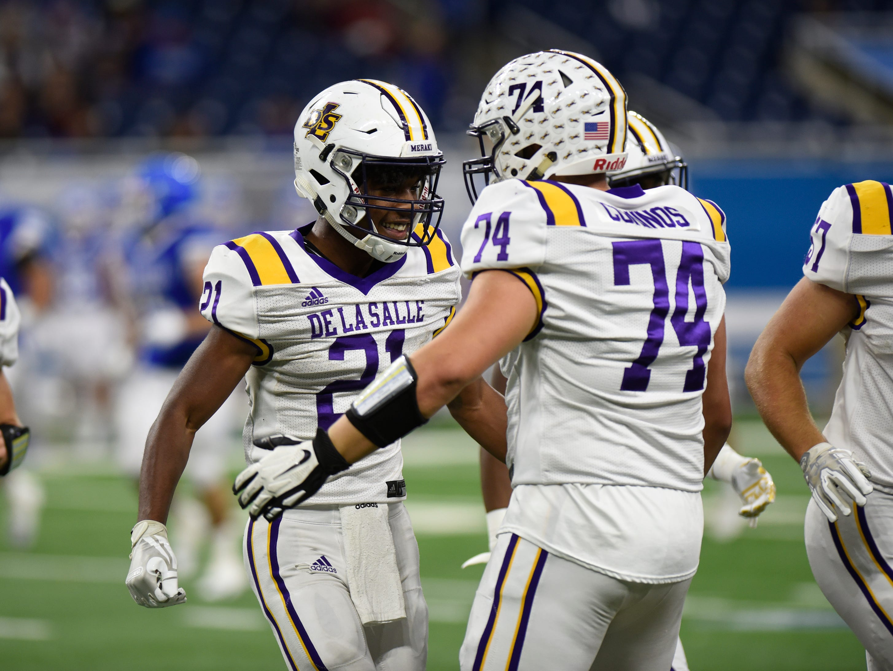 Warren De La Salle's Joshua DeBerry (21)is congratulated by Warren Christopher Cominos (74) after he intercepted a pass during Catholic League Prep Bowl AB Division championship game at Ford Field Oct. 20, 2018.