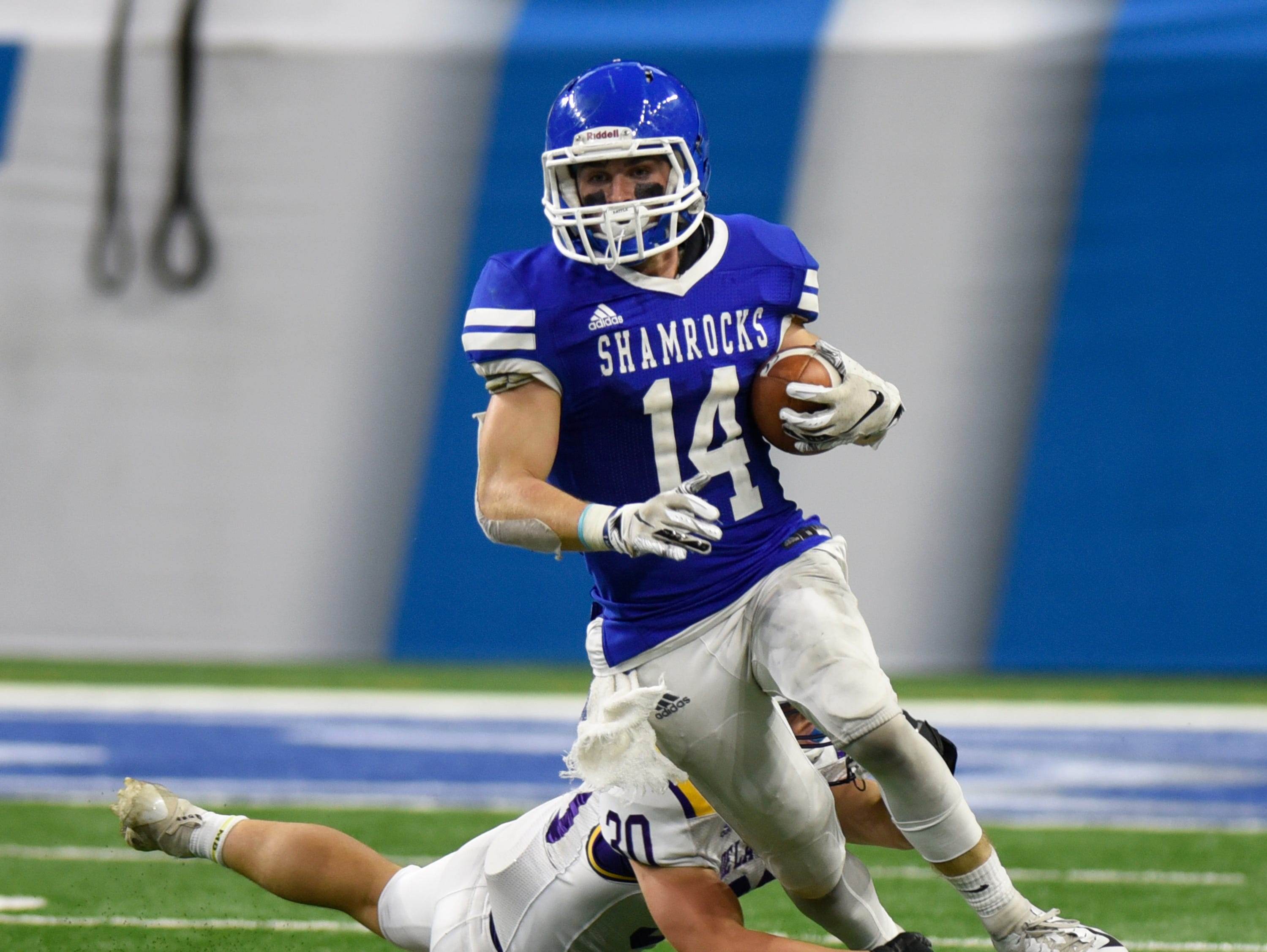 Detroit Catholic Central wide receiver Ryan Birney (14) is tripped up by Warren De La Salle's Brett Stanley during the Catholic League Prep Bowl AB Division championship game at Ford Field Oct. 20, 2018.