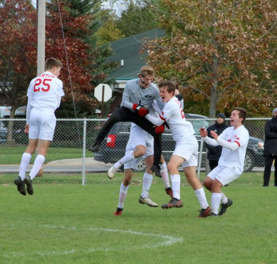 Canton senior goalkeeper Ian Nielsen is mobbed by teammates after stopping the final penalty kick.