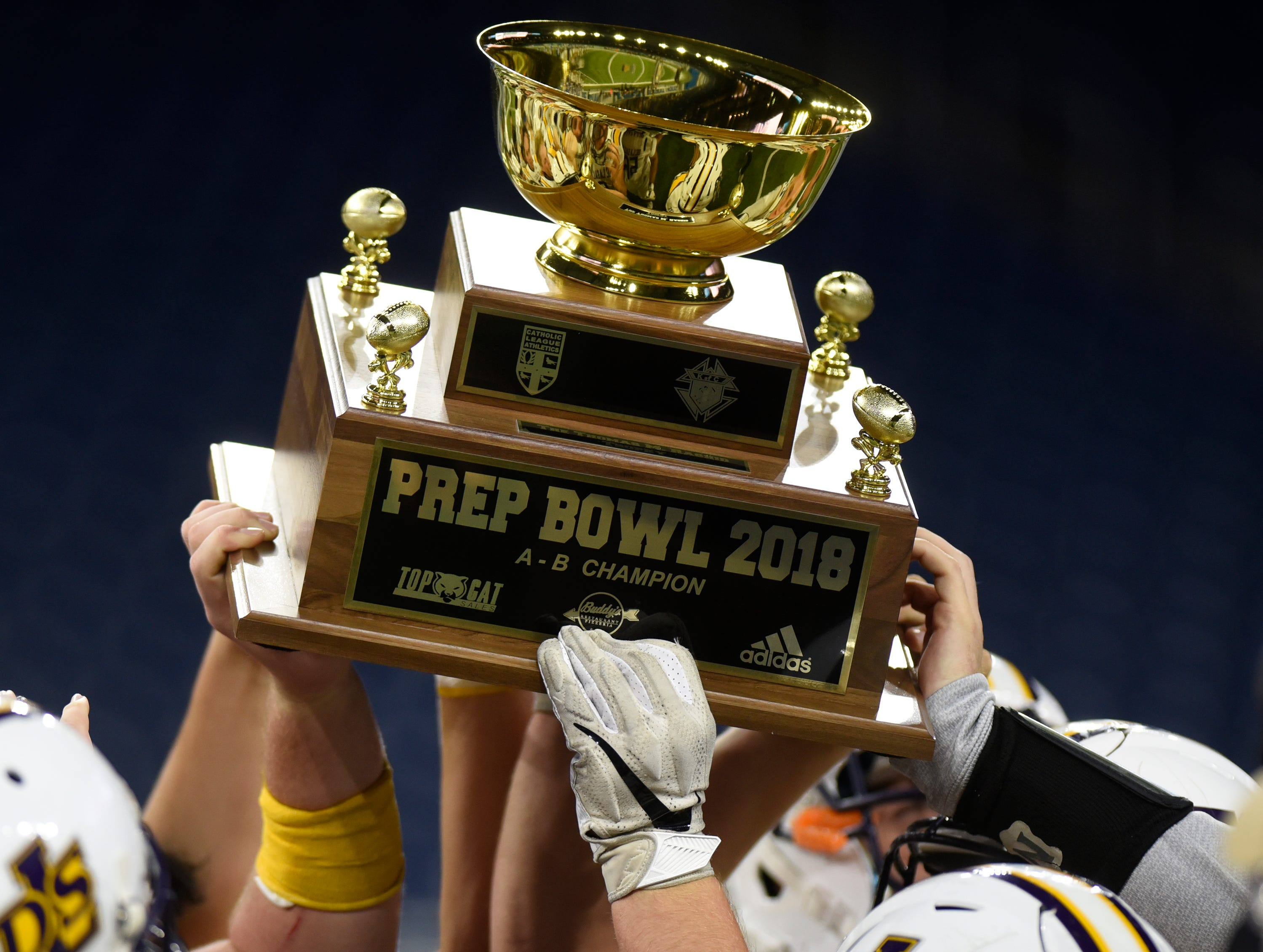 Warren De La Salle players hold up the championship trophy after defeating Detroit Catholic Central 24-6 in he Catholic League Prep Bowl AB Division title game at Ford Field Oct. 20, 2018.