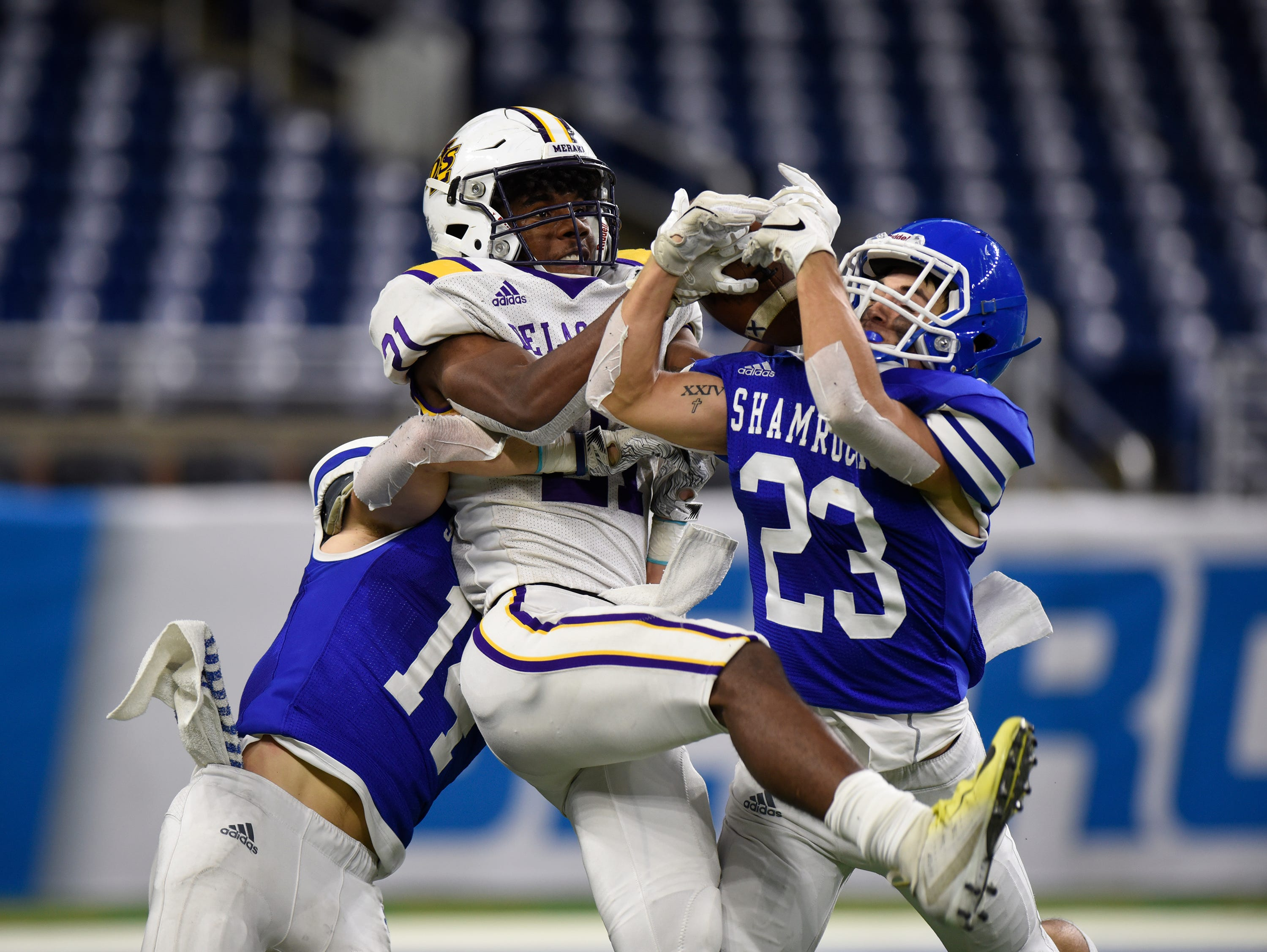 Warren De La Salle's Joshua DeBerry (21) was called for pass interference on this third quarter pass as Catholic Central receivers Detroit Catholic Ryan Birney and Parker Bohland (23) go for the ball during Catholic League Prep Bowl AB Division championship game at Ford Field Oct. 20, 2018.