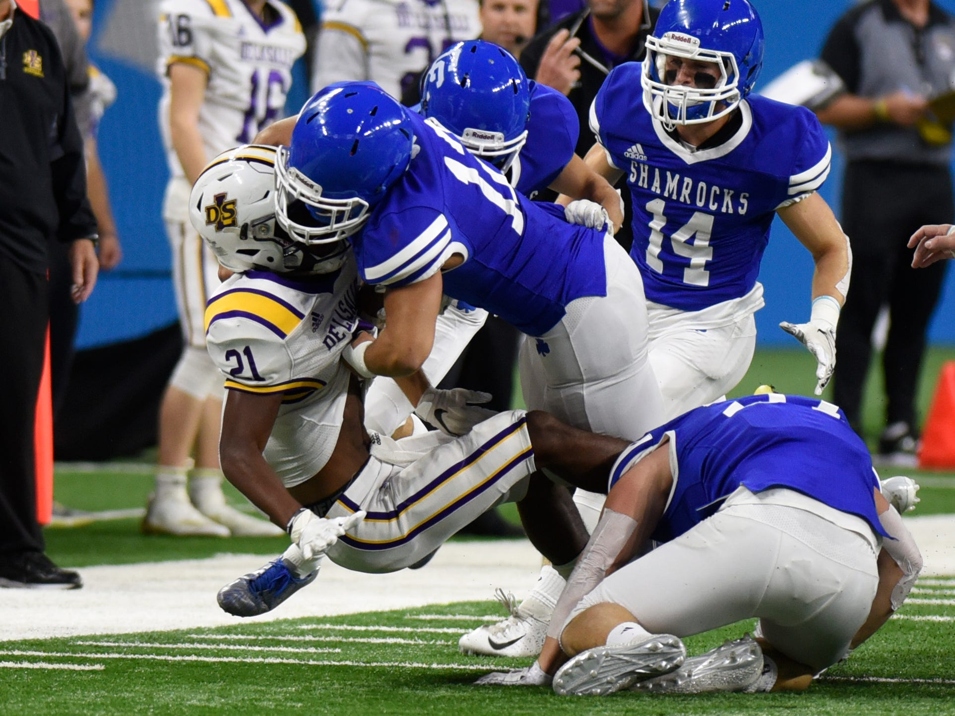 Warren De La Salle's Anthony Stepnitz is tackled by Detroit Catholic Central's Nate Anderson (11) during Catholic League Prep Bowl AB Division championship game at Ford Field Oct. 20, 2018.