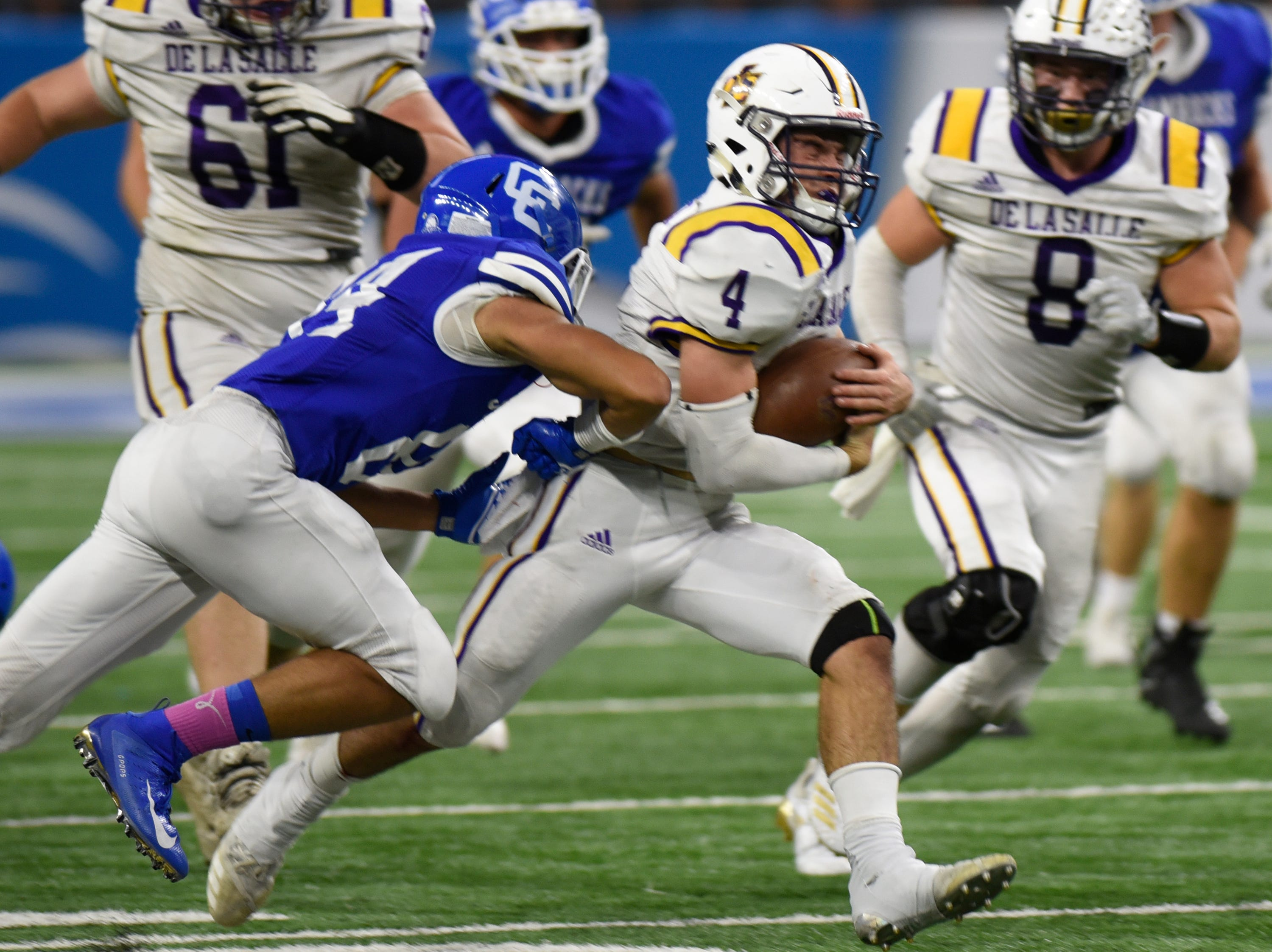 Detroit Catholic Central's Jonathan Brewer (84) can't bring down Warren De La Salle quarterback Nolan Schultz (4) as he runs 70 yards for a TD during the Catholic League Prep Bowl AB Division championship game at Ford Field Oct. 20, 2018.