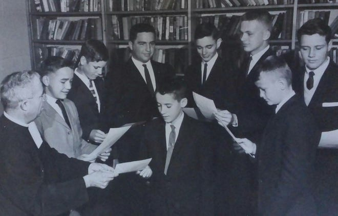 The AIC Boys Speech Club viewing certificates awarded at an area speech tournament. Pictured in front, from left, are Jimmy Genovese and Phil Castille. Back row from left are AIC Principal Brother Anthony, Chip McCardell, George Bakowski, Richard Lafleur, Jimmy Doherty, Ed Dubuisson, and Edwin Harmon.