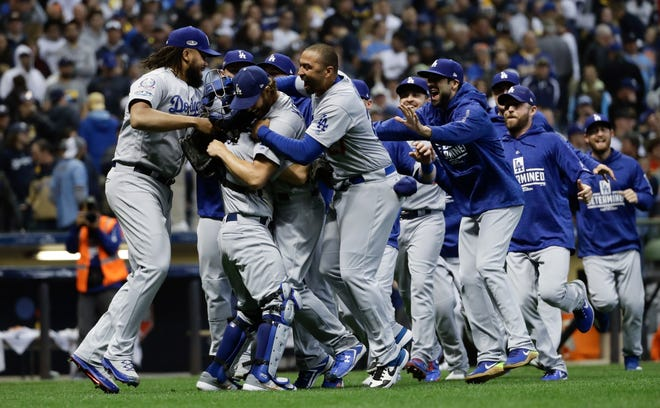 The Los Angeles Dodgers celebrate after Game 7 of the National League Championship Series baseball game against the Milwaukee Brewers Saturday, Oct. 20, 2018, in Milwaukee. The Dodgers won 5-1 to win the series. (AP Photo/Matt Slocum)