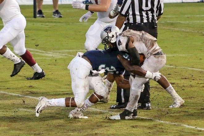 UWF's Alden McClellon (32) stops Florida Tech's Antwuan Haynes (6) in his tracks and drops him to the ground in the Coastal Classic rivalry game at Blue Wahoos Stadium on Saturday, October 20, 2018. Due numerous weather delays, the game started an hour and forty minutes after the originally scheduled time.