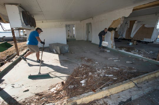 Chad Peacock and Olan Ward clean up the 13 Mile Seafood Market just outside of Apalachicola on Sunday, more than a week after Hurricane Michael ripped through the area.