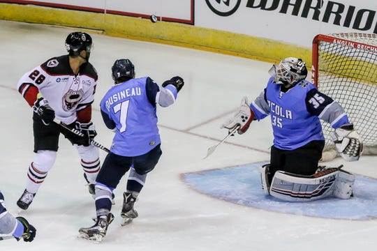 Pensacola's Josh Cousineau (7) and Birmingham's Loren Ulett (26) watch the puck after it was deflected by goalie Andrew D'Agostini (35) in the Ice Flyers' season home opener on Saturday, October 20, 2018, at the Pensacola Bay Center. The Ice Flyers led 2-0 in the second period, but the Bulls scored three unanswered goals to win the game in front of over 7,200 fans, the largest home opener in the team's history.