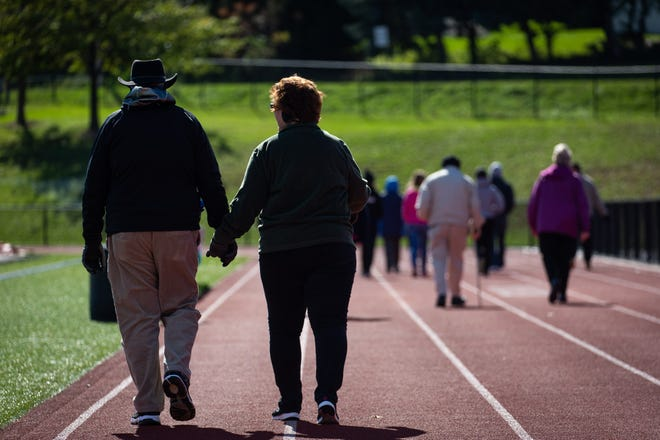 Alison Parker, right, and Lynn Parker, left, hold hands as they walk three miles on the South Western High School track while taking part in the 42nd annual Hanover Area CROP Walk, Sunday, Oct. 21 in Hanover.