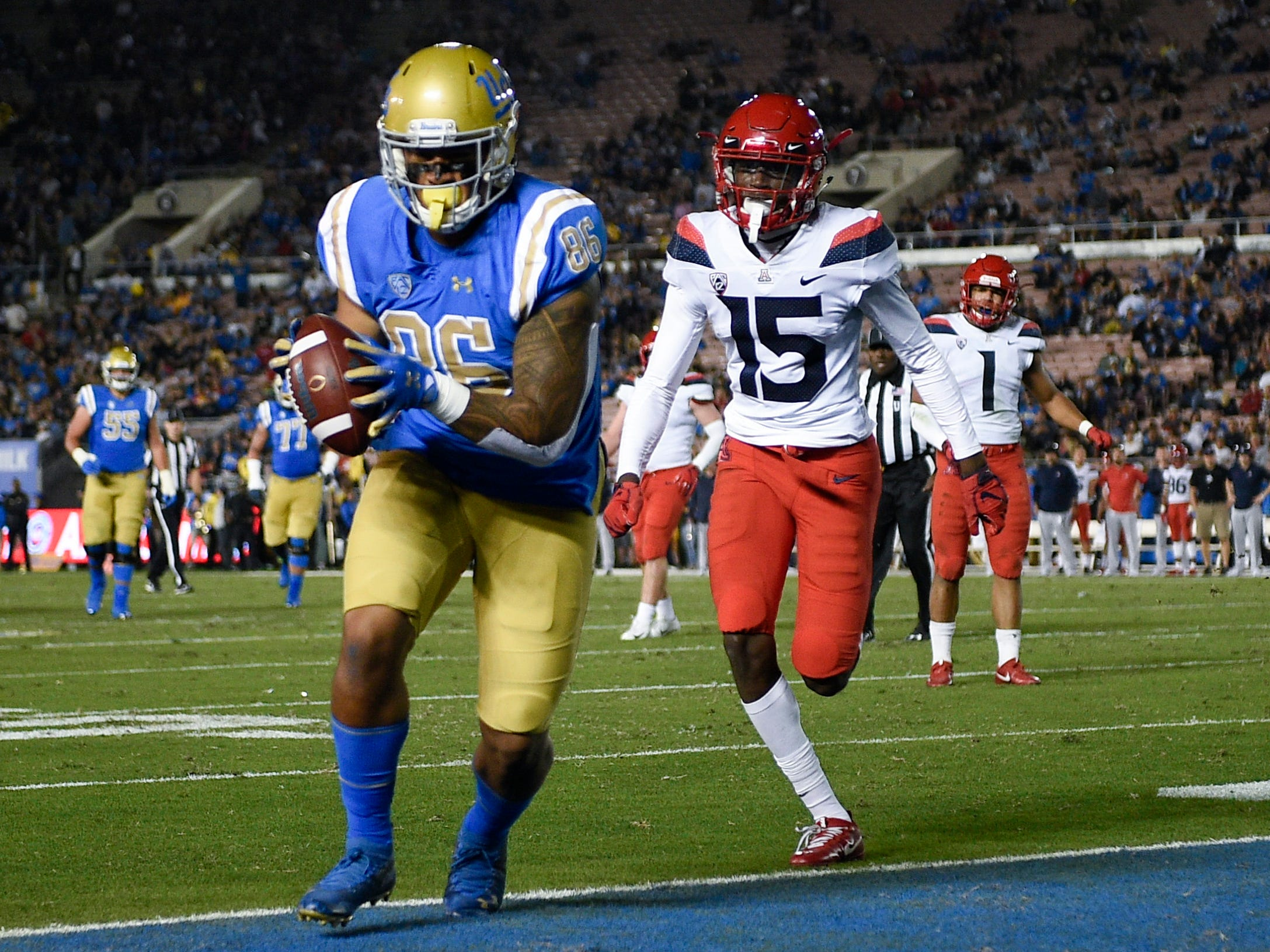 Oct 20, 2018; Pasadena, CA, USA; UCLA Bruins tight end Devin Asiasi (86) catches a pass for a touchdown defended by Arizona Wildcats cornerback McKenzie Barnes (15) during the first half at Rose Bowl. Mandatory Credit: Kelvin Kuo-USA TODAY Sports