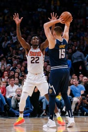 Deandre Ayton defends Nuggets center Nikola Jokic during the fourth quarter of a game Saturday at the Pepsi Center.