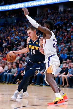 Suns center Deandre Ayton defends Nuggets big man Nikola Jokic during the second quarter of a game Saturday at the Pepsi Center.