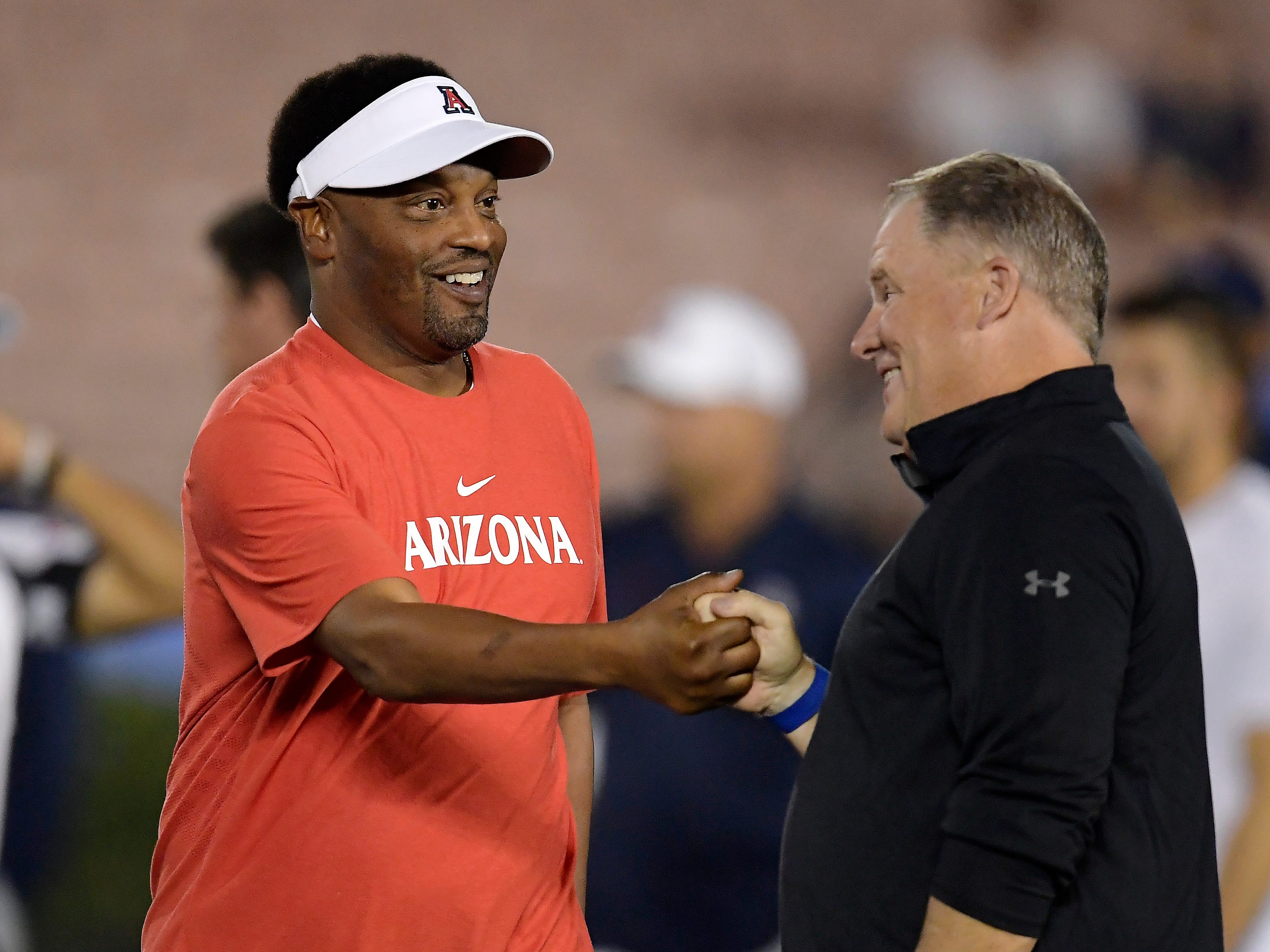 Arizona head coach Kevin Sumlin, left, talks with UCLA head coach Chip Kelly prior to an NCAA college football game Saturday, Oct. 20, 2018, in Pasadena, Calif. (AP Photo/Mark J. Terrill)
