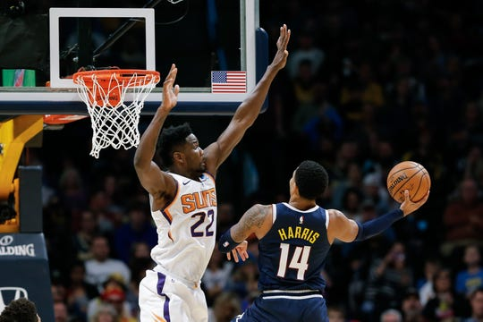 Nuggets guard Gary Harris drives against Suns center Deandre Ayton during a game Saturday at the Pepsi Center.