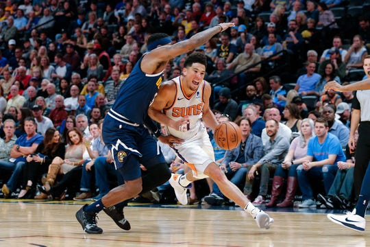 Suns guard Devin Booker is defended by Nuggets forward Torrey Craig during the third quarter of a game Saturday at the Pepsi Center.
