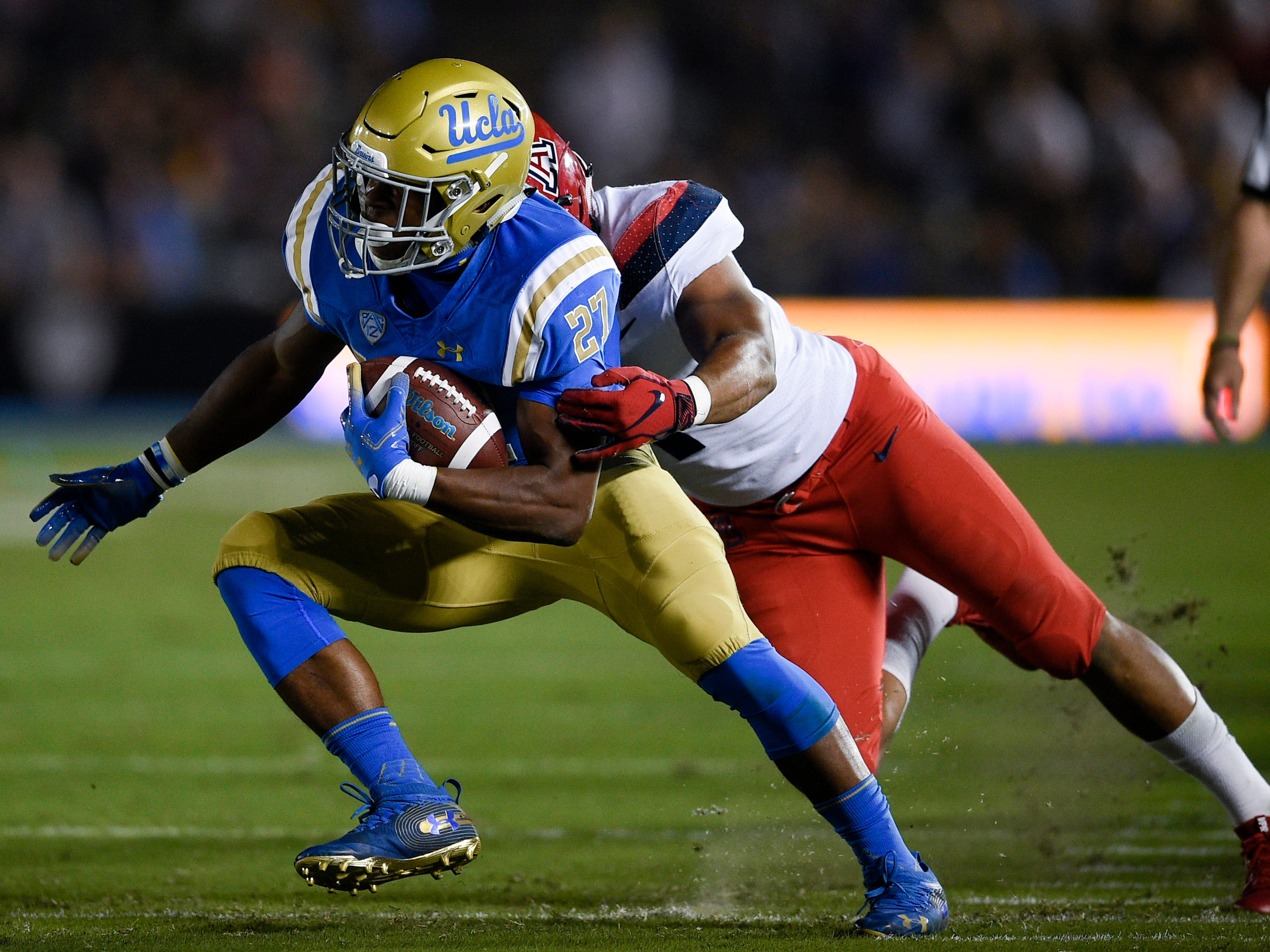 Oct 20, 2018; Pasadena, CA, USA; UCLA Bruins running back Joshua Kelley (27) runs the ball defended by Arizona Wildcats linebacker Tony Fields II (1) during the first half at Rose Bowl. Mandatory Credit: Kelvin Kuo-USA TODAY Sports