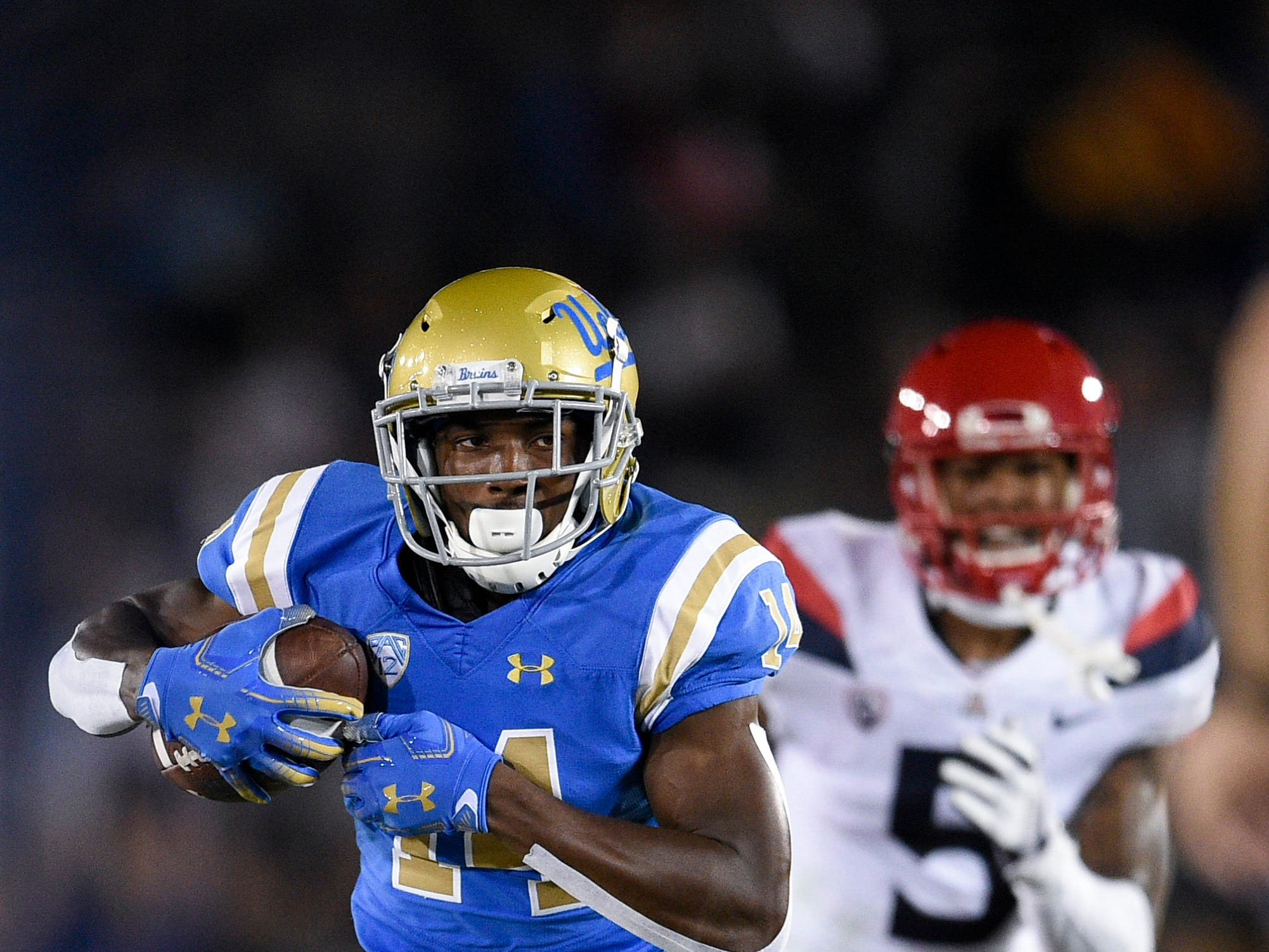 Oct 20, 2018; Pasadena, CA, USA; UCLA Bruins wide receiver Theo Howard (14) runs the ball after the catch ahead of Arizona Wildcats safety Christian Young (5) during the first half at Rose Bowl. Mandatory Credit: Kelvin Kuo-USA TODAY Sports