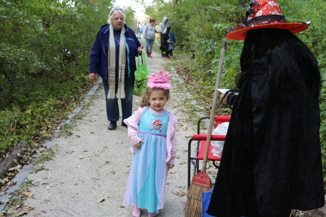 "Kayleigh Camp, 3, trick-or-treats through the Ottawa National Wildlife Refuge during their annual ""Howl-o-ween"" on Saturday."