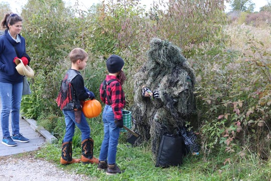 "Avery and Zale Kutkowski trick-or-treat through the Ottawa National Wildlife Refuge during their annual ""Howl-o-ween"" on Saturday."