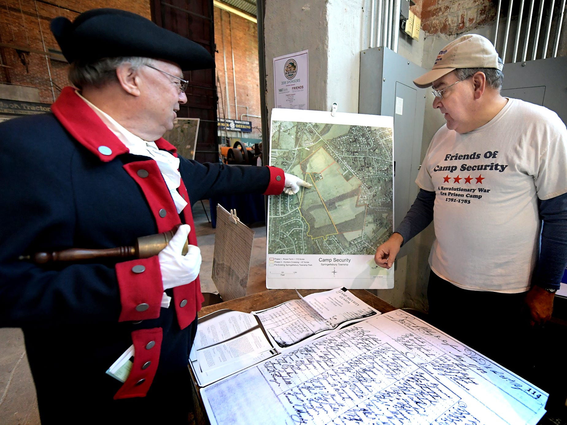 York County History Center volunteer Tom Gibson, as the York Town Crier, talks with Jonathan Stayer, Friends of Camp Security member, at a camp presentation at the Agricultural & Industrial Museum during the History On The Half Shell fundraising event sponsored by the center Sunday, October 21, 2018. The annual event offered oysters, a variety of food, drink, music, children's activities and historical presentations. Bill Kalina photo