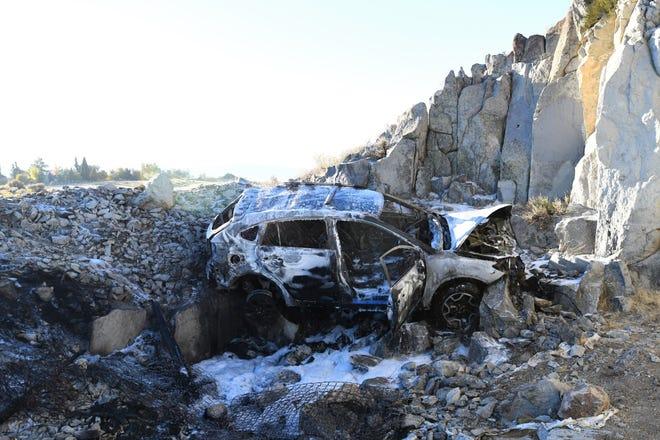 A burned-up Subaru Crosstrek lodged on rocks in a ditch near a neighborhood north of McCarran Boulevard on Sunday, Oct. 21, 2018.