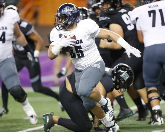 Nevada running back Toa Taua breaks through the Hawaii defense during the third quarter Saturday night.