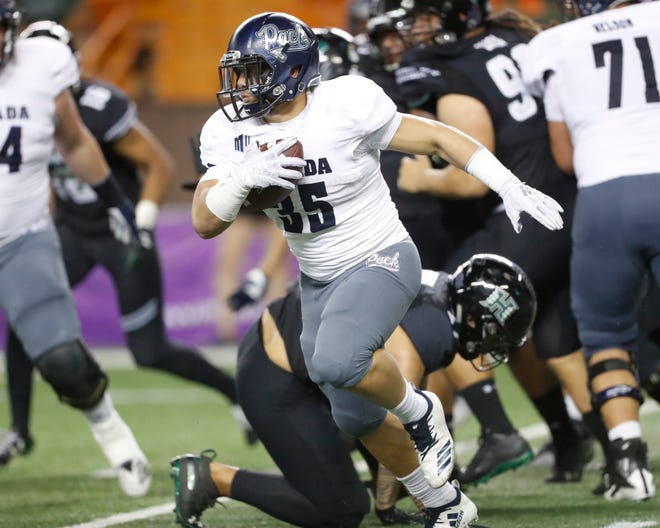 Nevada running back Toa Taua breaks through the Hawaii defense during the Wolf Pack's win last season.