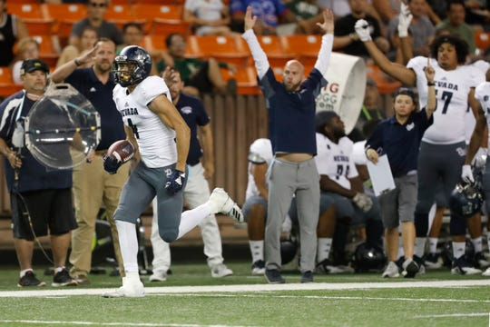 As the Nevada bench cheers, Nevada wide receiver Elijah Cooks runs in for a third quarter touchdown against Hawaii on Saturday night.