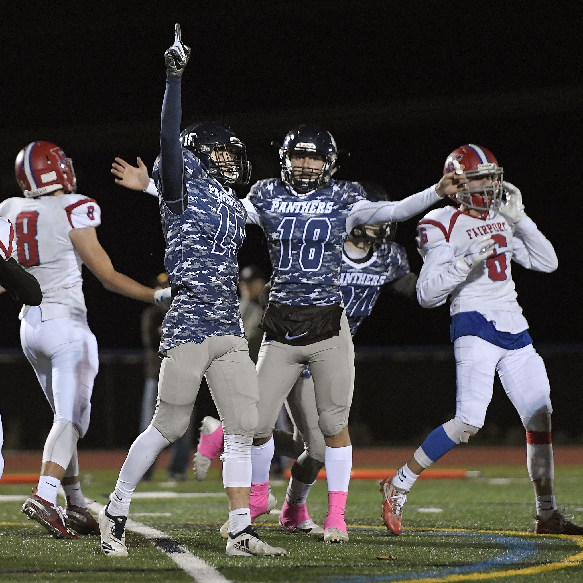 Pittsford kicker Kyle Hennessey, pointing, celebrates his game-winning extra point with holder Tyler Love during after Pittsford defeated Fairport 28-27 in overtime Saturday night to advance to the semifinals against Aquinas.