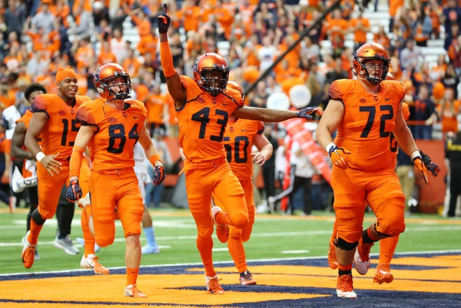Oct 20, 2018; Syracuse, NY, USA; Syracuse Orange players rush the field following their overtime victory against the North Carolina Tar Heels at the Carrier Dome. Mandatory Credit: Rich Barnes-USA TODAY Sports