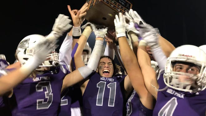 Shasta linebacker Isaiah Pena (11) hoists the River Bowl after the Wolves defeated Enterprise, 47-10.