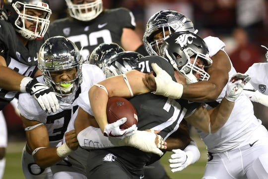 Oct 20, 2018; Pullman, WA, USA; Washington State Cougars running back Max Borghi (21) is gang tackled by the Oregon Ducks in the second half at Martin Stadium. The Cougars won 34-20. Mandatory Credit: James Snook-USA TODAY Sports