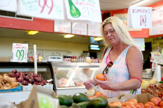 Tina Clark, of Salem, picks out tomatoes at Norman's Farmers Market and Gillespie's Meat Shoppe in Salem on Saturday, Oct. 20, 2018. Oregon Measure 103 would make future grocery taxes unconstitutional.