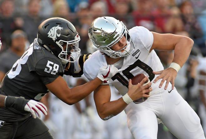 Oct 20, 2018; Pullman, WA, USA; Oregon Ducks quarterback Justin Herbert (10) is sacked by Washington State Cougars linebacker Fa'avae Fa'avae (58) in the first half at Martin Stadium. Mandatory Credit: James Snook-USA TODAY Sports