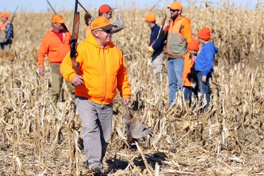 Bill Crawford of Watertown carries a pheasant after walking a cornfield during last year's pheasant opener near Zell, S.D.