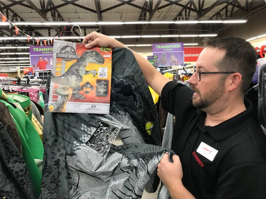 Jeff Pelzer, manager of Savers in Sioux Falls, shows off a Jurassic Park velociraptor costume he's selling at his store.