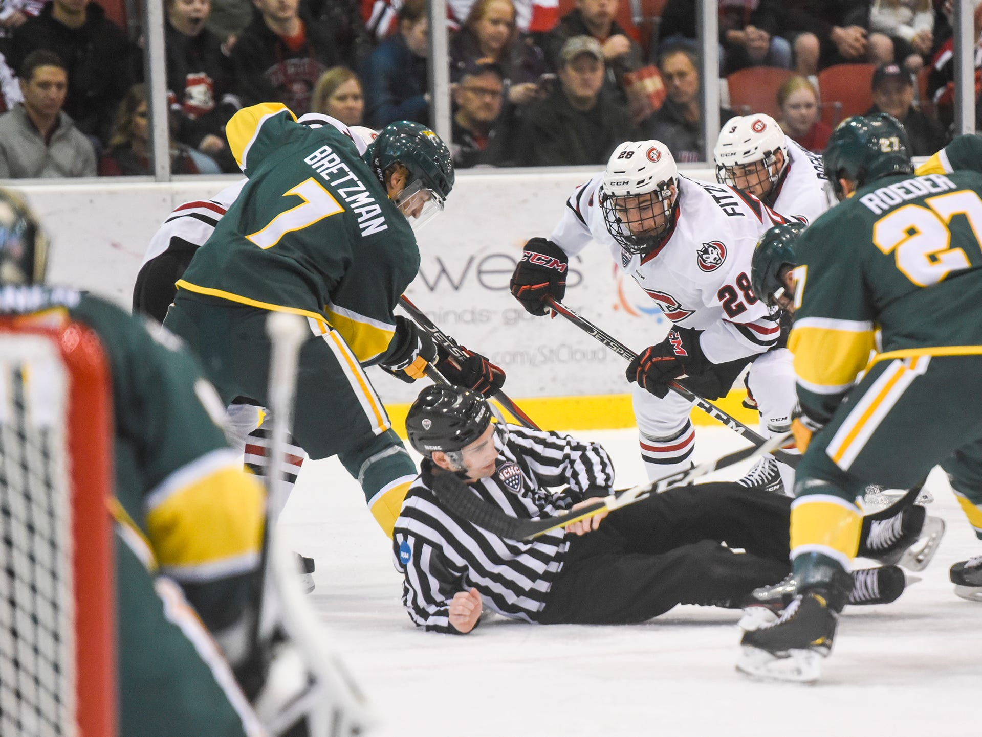 An official gets tangled with players on the ice during the Saturday, Oct. 20, game at the Herb Brooks National Hockey Center in St. Cloud.