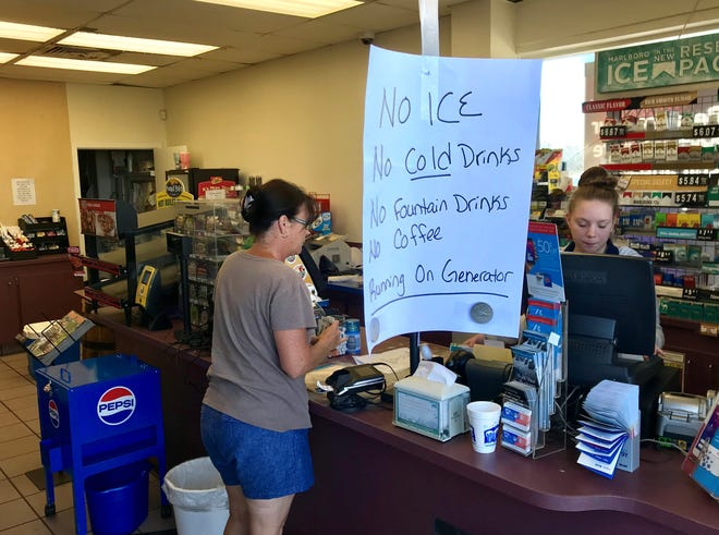 Nicole Campbell rings up a customer at the Handi Mart on Highway 69 in Grand Ridge. The store reopened Saturday after getting a generator to run cash registers and fuel pumps.