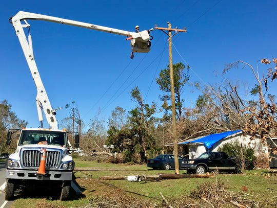 A lineman from North Carolina-based Pike Electric Corp. makes repairs Sunday in Grand Ridge. Power has been out to the entire town since Hurricane Michael made landfall.